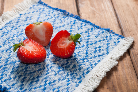 Fresh strawberries on old wooden background, cut berry patterned on a napkin