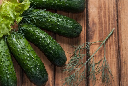 white washed: Fresh cucumbers on wooden background. Whole cucumbers, green salad . Stock Photo