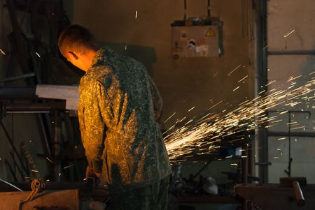 forge: Man sawing metal with disk grinder, the work in the forge