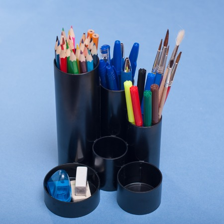 Black holders for office supplies with them on a blue background, an organizer with stationery Stock Photo