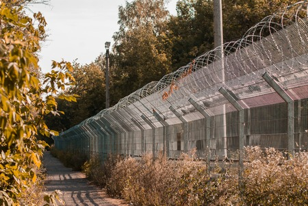 Long fence with barbed wire, the protection of refugees