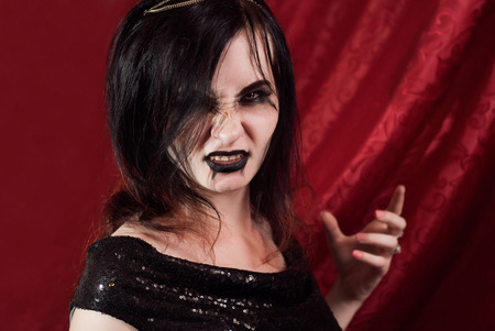 Aggressive female vampire, a brunette with Gothic makeup