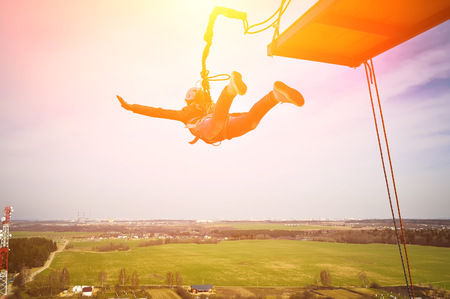 Rope jumping or bungee jumping, girl jumping to the bottom, extreme background Stock Photo