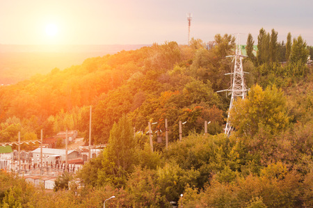 substation on sunset background, electric pole among the trees in autumn, Stock Photo