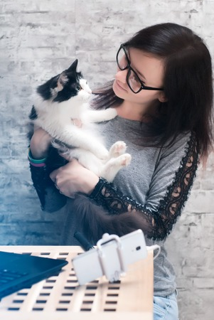 assignments: girl hugging her cat during a pause of the stream laptop, smartphone and selfie stick on the table