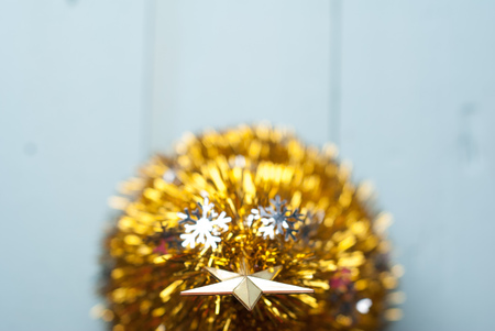 Christmas gold star on the tree top view, blue wooden background