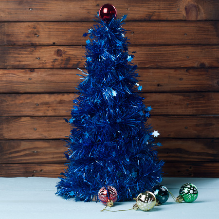 Christmas Tree with their hands, blue tinsel, and a set of decorative balls