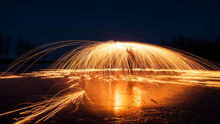 Bright sparks from the steel wool, creative photographing at night, the reflection on the ice