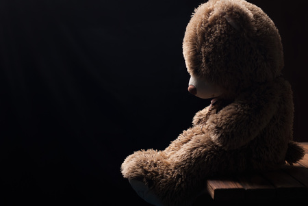 A lone Teddy bear sitting in the dark, side view, forgotten toy