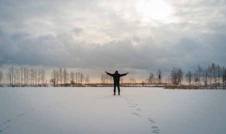 Unity of man and nature, man spread his hands to the sides in winter, dramatic winter landscape, Hiking in the snow