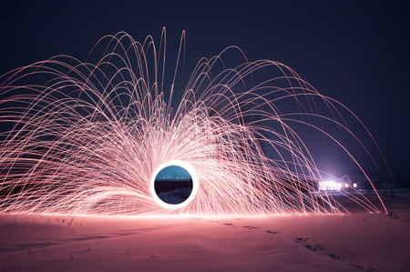 steel wool photo, a Mysterious portal of sparks in the winter night, a black hole, strange things happen this night 写真素材