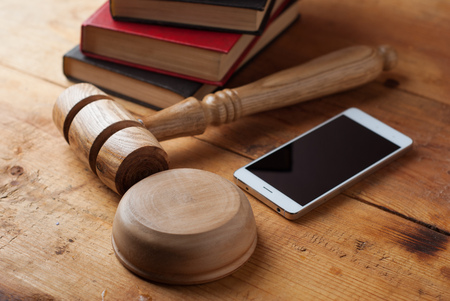 smartphone, the judges gavel on wooden background. Digital gadget. Illegal access to computer information,distribution of malicious programs. Violation of the secrecy of correspondence Stok Fotoğraf