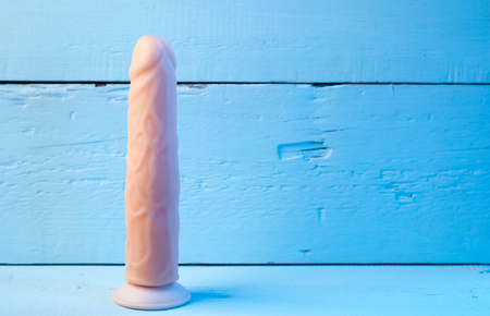 Realistic vibrator on a blue background, Showcase in a sex shop, toys for adults