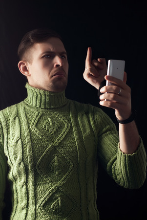 The concept of a telephone quarrel, hipster in a green sweater holds a smartphone, an emotional face