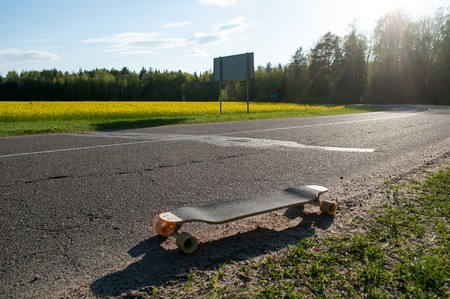 long Board on the asphalt road in a rural background, a yellow field of rapeseed, an adventure on a longboard