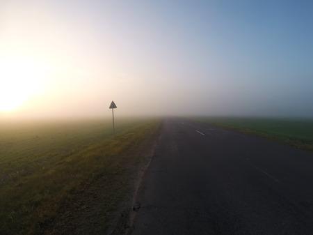 Foggy road at dawn, thick fog, Archivio Fotografico