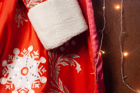 Close-up of red Santa Claus fur coat, Santa clothes and garland, new year background, 版權商用圖片