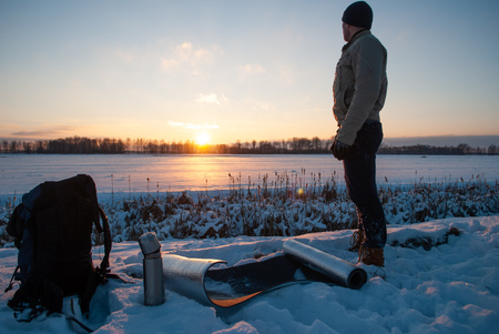 Man watching the sunset in the winter evening, winter tourism, camping in the snow