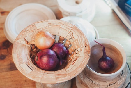 Raw onions in decorative dishes, rustic style, top view,