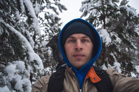 a man in a blue hood takes a selfie in the winter forest on the background of snow-covered trees, a walk in the winter forest, unity with nature,