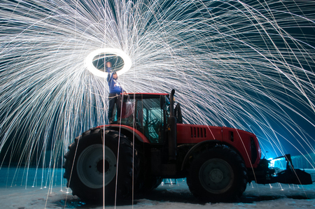 Man sparks on the background of a red tractor, steel wool photo, sparks on a long exposure,