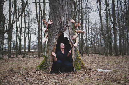 The dark and mysterious forest, a scared person hiding under a tree, hands behind the tree are drawn to a person, the concept of human fear, Imagens