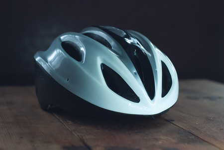 Bicycle helmet on wooden table, white plastic helmet on dark background, protection for cyclist, Imagens