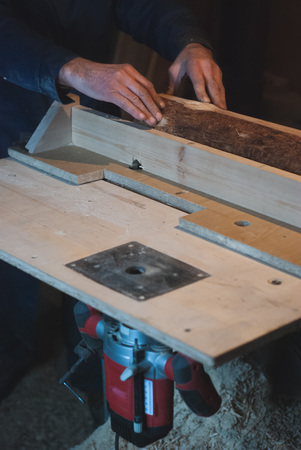 Hands of an old carpenter, in working overalls equates a wooden bar with a milling machine in the workshop, production small business,