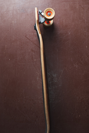 Skateboard on orange background, symbol of urban subculture, curved longboard with white wheels,