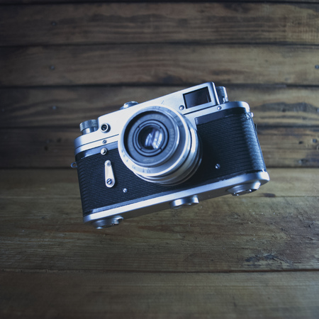 Retro camera in the air on the background of old wooden background, vintage metal camera hovering in the air, Imagens