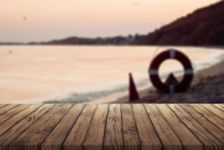 old wooden table for advertising your products, wooden table against the sea at sunset, the concept of marine rescuers Imagens