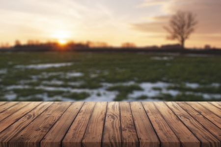 free space for your advertising, old wooden table on the background of early spring, rural landscape at sunset in blur mode, Easter table