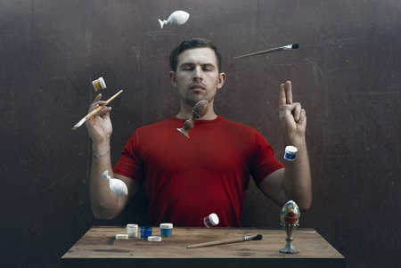 the Creator makes objects fly, the concept of preparation for Easter, a set of wooden homemade eggs, paint and brushes, a creative person in a red t-shirt