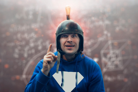 Close-up portrait Of a young man with a surprised look, a scientist in a helmet with a light bulb having a great innovative idea, pointing a finger at the sign of Eureka, an old vintage helmet idea generator