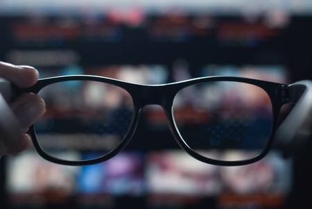 hand holding black glasses on the background of the monitor, vision deteriorated due to the long stay at the computer, poor vision and glasses do not help