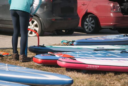 Sporty girl pumps paddle Board, a new kind of outdoor activity on the water Banco de Imagens