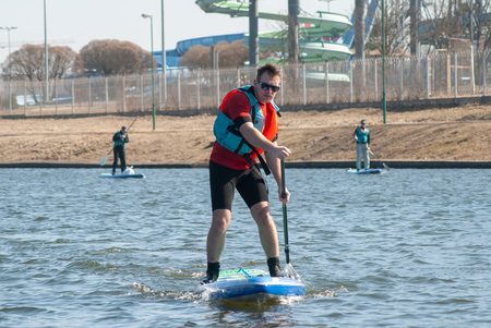 Athlete rowing on the Board paddle, outdoor activities on the water, a sports man with a paddle,