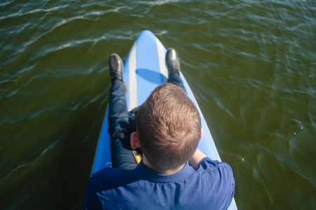 Businessman on a surfboard, a Young man in a shirt and shoes floating on the river on a paddleboard, the concept of finding opportunities, the idea of opening new horizons, Imagens