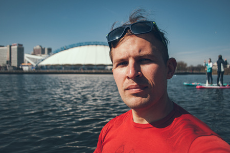 Open air Selfie of a young boy in Sunny day on background of the city. A man in a red t-shirt having fun together on a paddleboard on a warm day,