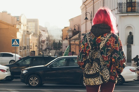 Cute hipster girl with pink hair, on the background of the morning city, bright casual clothes, stylish backpack. The concept of street fashion,