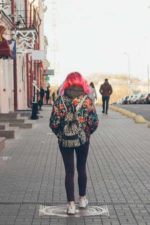 Cute hipster girl with pink hair is walking around the city, bright casual clothes, stylish backpack. The concept of street fashion, Imagens