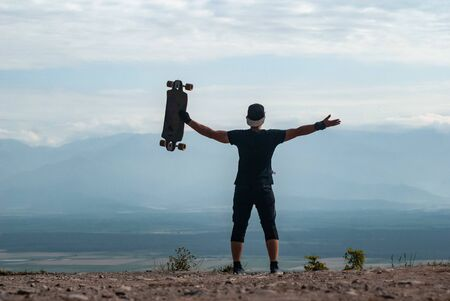 A young man in a cap with a Board in his hands stands on a cliff high in the mountains against the sky, a journey on a skateboard, Banque d'images