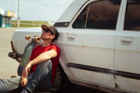 Young skater in the red shirt resting at the old cars, the journey to longbone Фото со стока