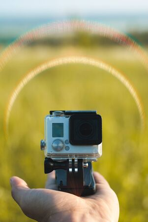 small action camera on nature background, advertising template