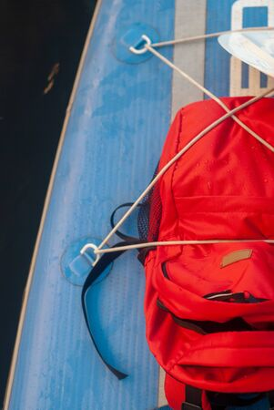 Red backpack on puddle Board, Sports travel backpack closeup. 写真素材