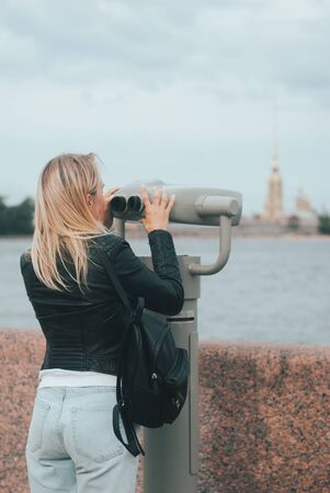 blond girl looks through a telescope at the sights of St. Petersburg, the observation deck in the city,