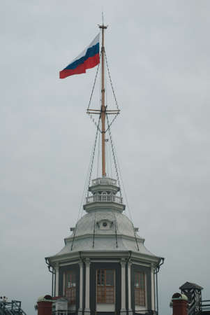 The flag of Russia is a national symbol in the wind. The Russian flag flutters in the wind against a white cloudy sky. Russian flag on the flagpole