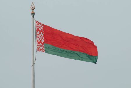 The flag of Belarus develops in the wind against the background of a white cloudy sky. Belarusian flag.