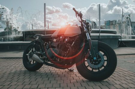 Black cool motorcycle on the background of the city at sunset, Stok Fotoğraf