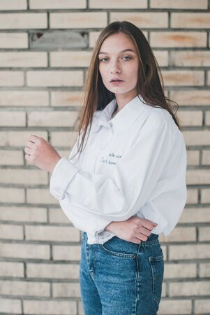 Young girl in white shirt posing against brick wall